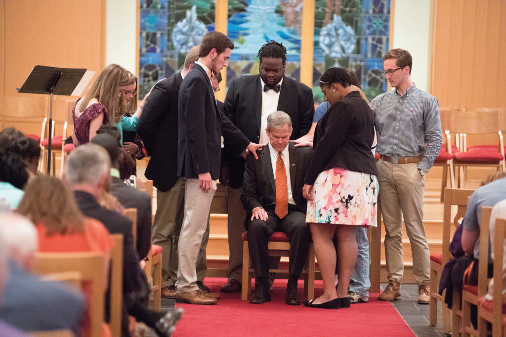 image of dr. creed praying with students