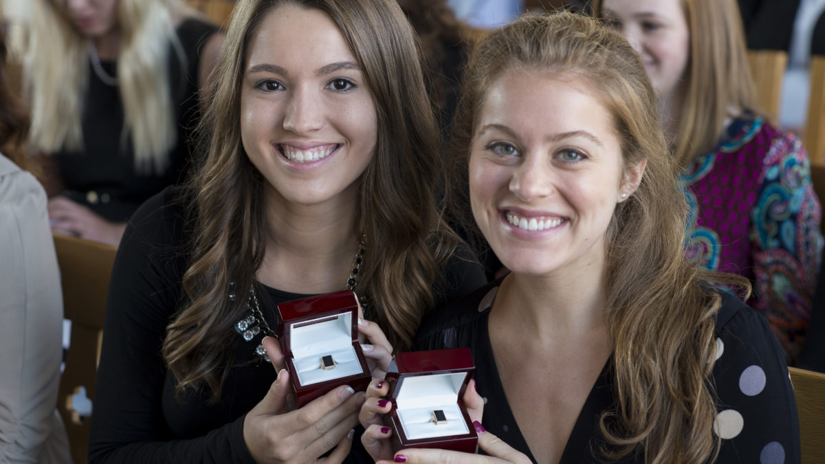 two female students pose with class rings