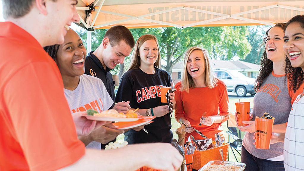 students laugh at homecoming tailgate