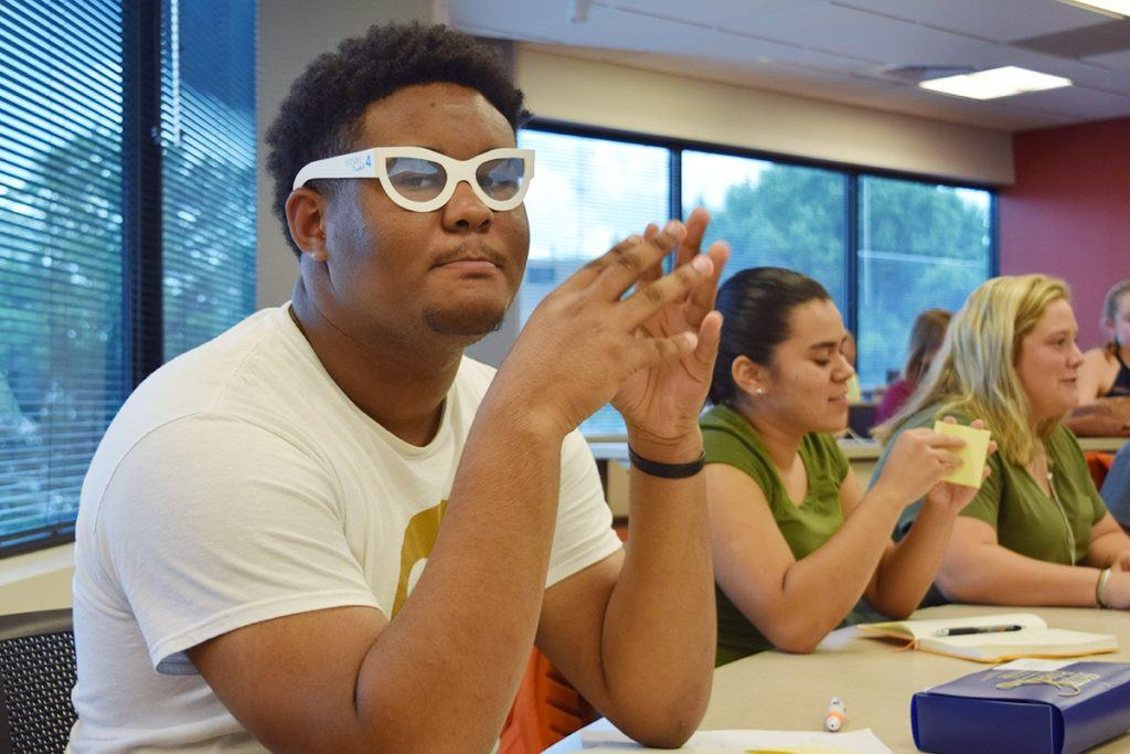 Male student with glasses participates in classroom session