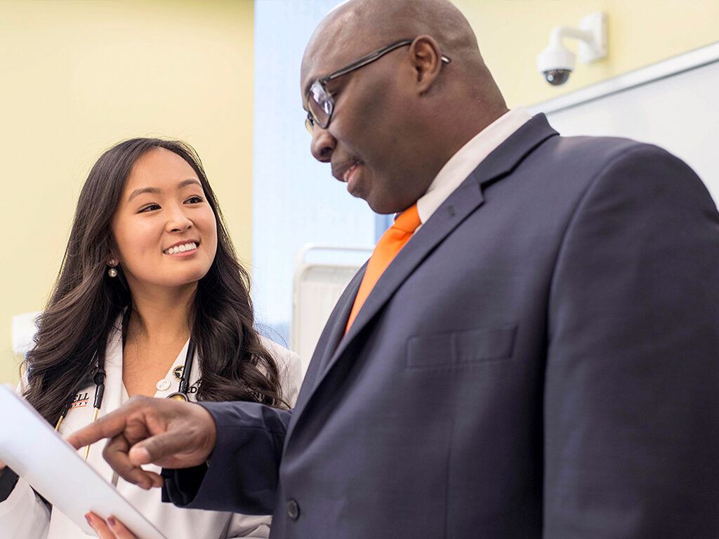 Image of student having conversation with professor in classroom