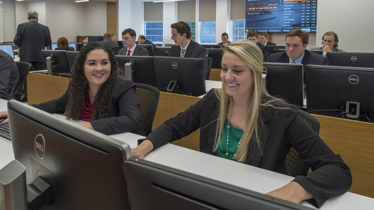 Two female Trust & Wealth Management students chat during class in the Trust & Wealth Management Center.