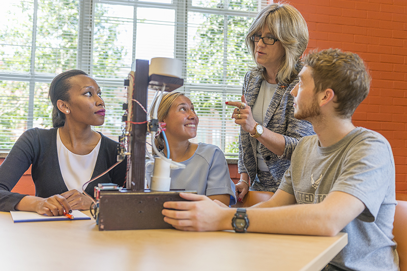 Engineering Dean Jenna Carpenter gets three student excited about an upcoming lab.