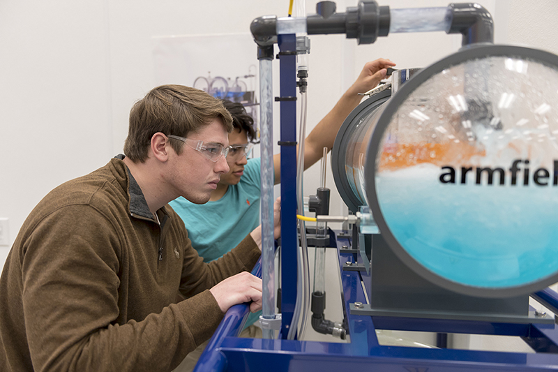 Two male engineering students work in the lab.