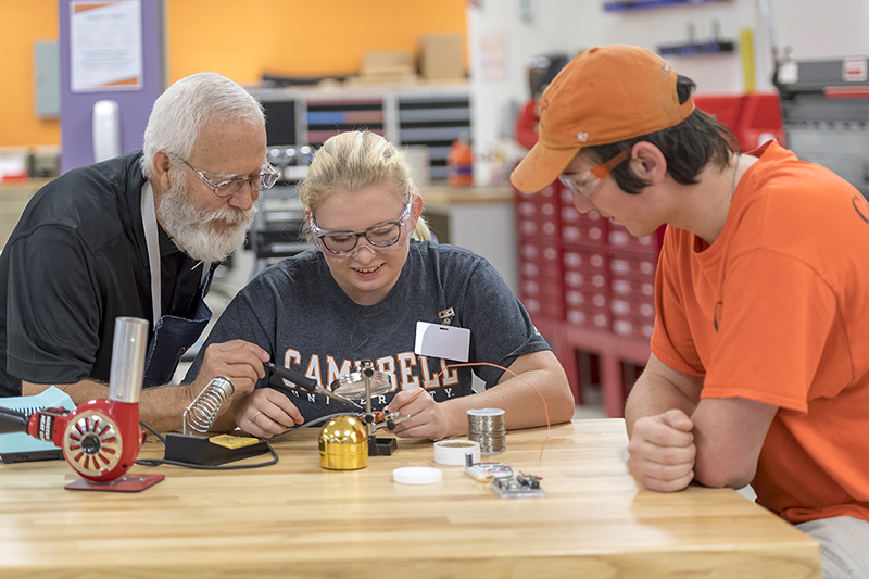 A female and male engineering student receive help from a professor during a lab.