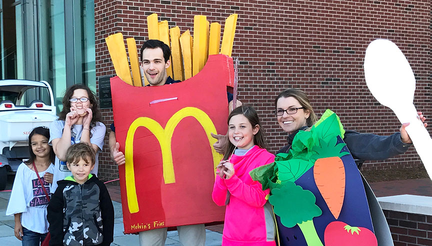 Second-year med students Seth Thomas (Mr. French Fry) and Shannon Norland (Ms. Salad) smile after a skit about healthy choices at the medical school's Community Field Day.
