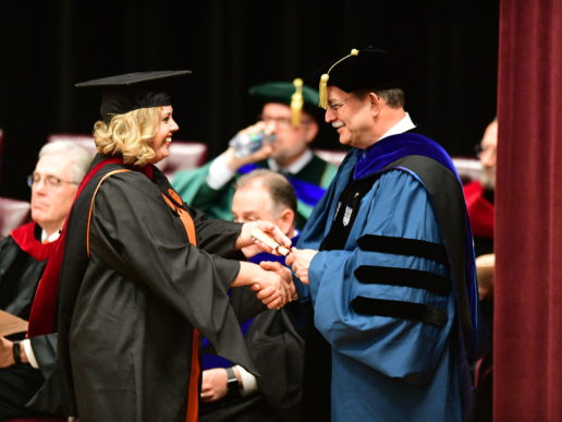 Photo of a Campbell Divinity graduate receiving her her hood