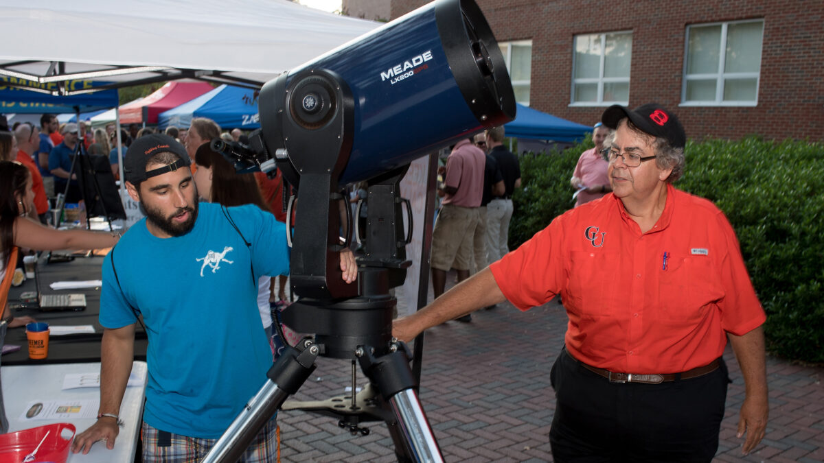 Photo of Jason Ezell and student explaining one of the university's telescopes.