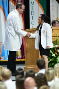 Dr. Adams shaking hand of student