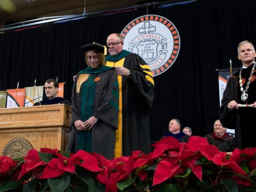 Student receives hood at graduation