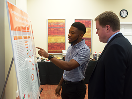 Philip Oji presents his research using a poster