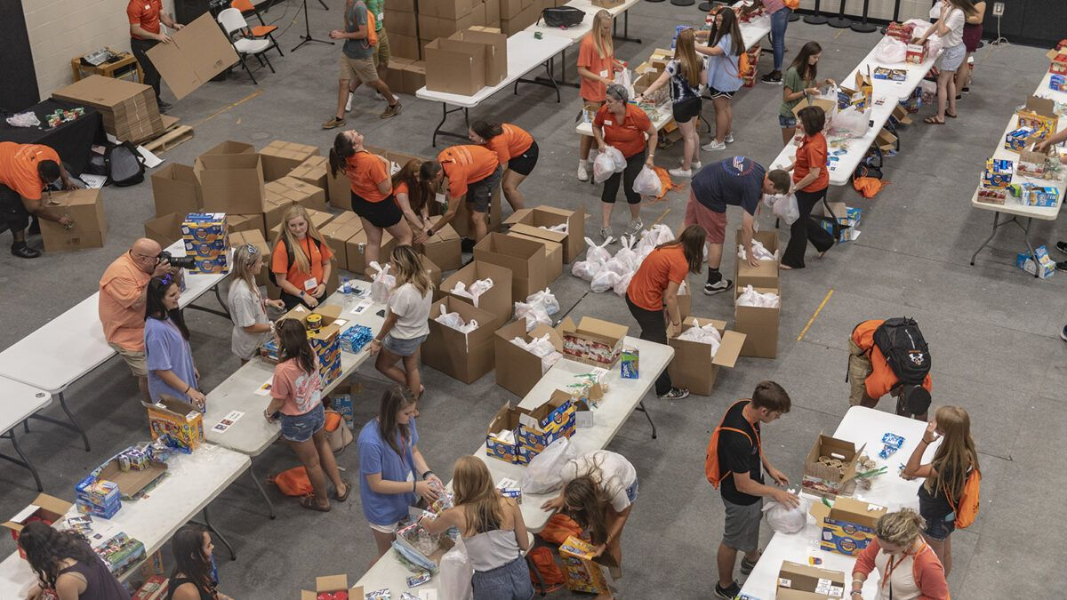 an overhead shot of a large room full of tables, at which students wearing orange are packing boxes full of supplies