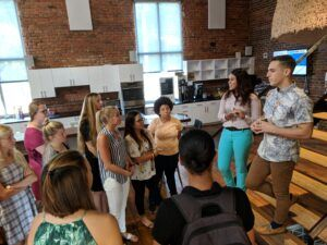 Side view of students gathered around Tom Jacobs in the brick-and-hardwood of the HQ Raleigh space.