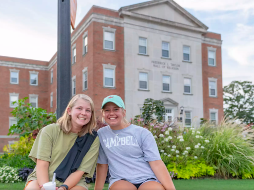 two blond-haired girls smile at camera, seated on a bench in front of Butler Chapel