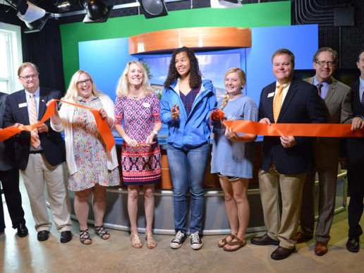 Students, faculty and WTVD staff stand in a line with the orange ribbon in the tv studio