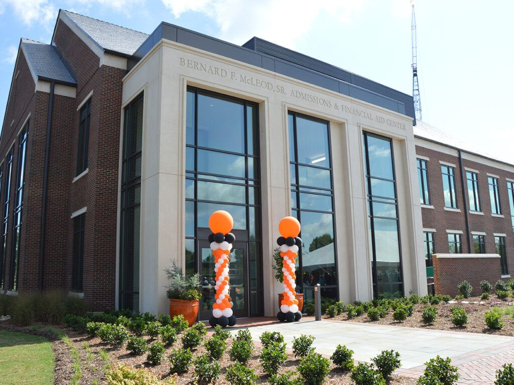 The facade of the new admissions building, with orange and black balloons at the doorway.