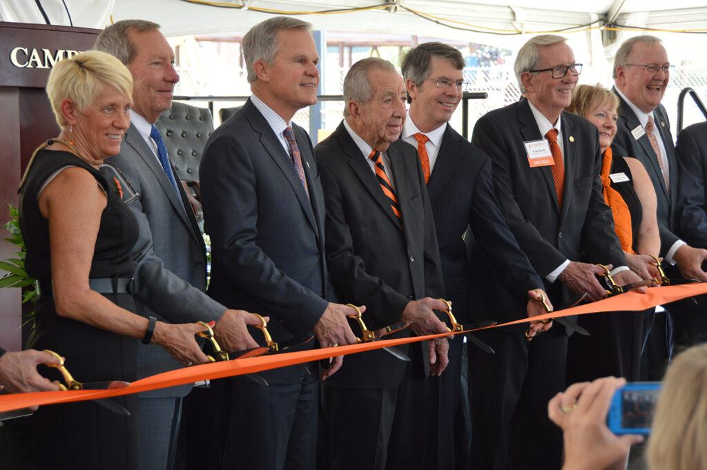 Dr. Creed, Bernard McLeod, and other trustees stand in a line with their scissors poised to cut an orange ribbon at the ceremony.