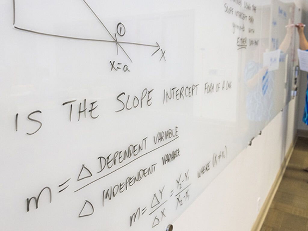 A whiteboard with engineering equations written on it in black marker. At the far end of the board is a woman in blue, writing on the board.