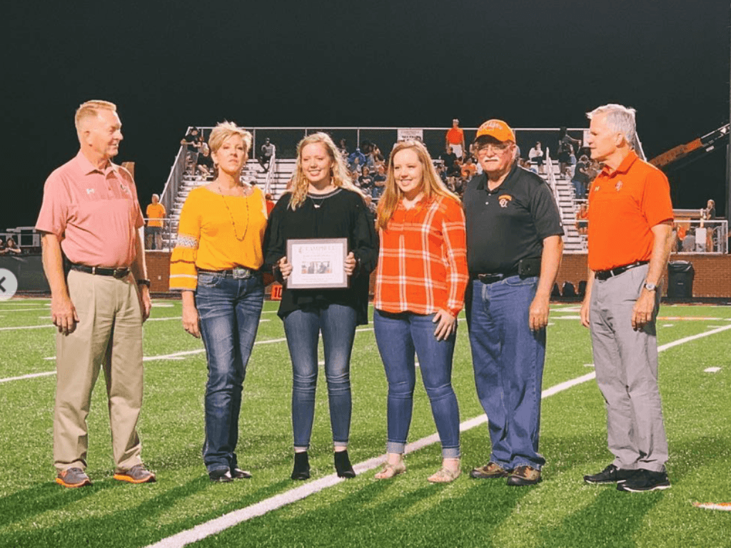 Dennis Bazemore, the four members of the Gaskins' family, and President Creed stand in a line on the football field. Savannah Gaskins, in the center, holds a certificate.