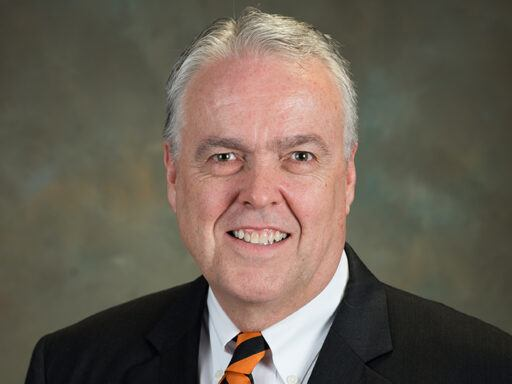 Headshot of Peter Donlon in a suit and orange-striped tie.