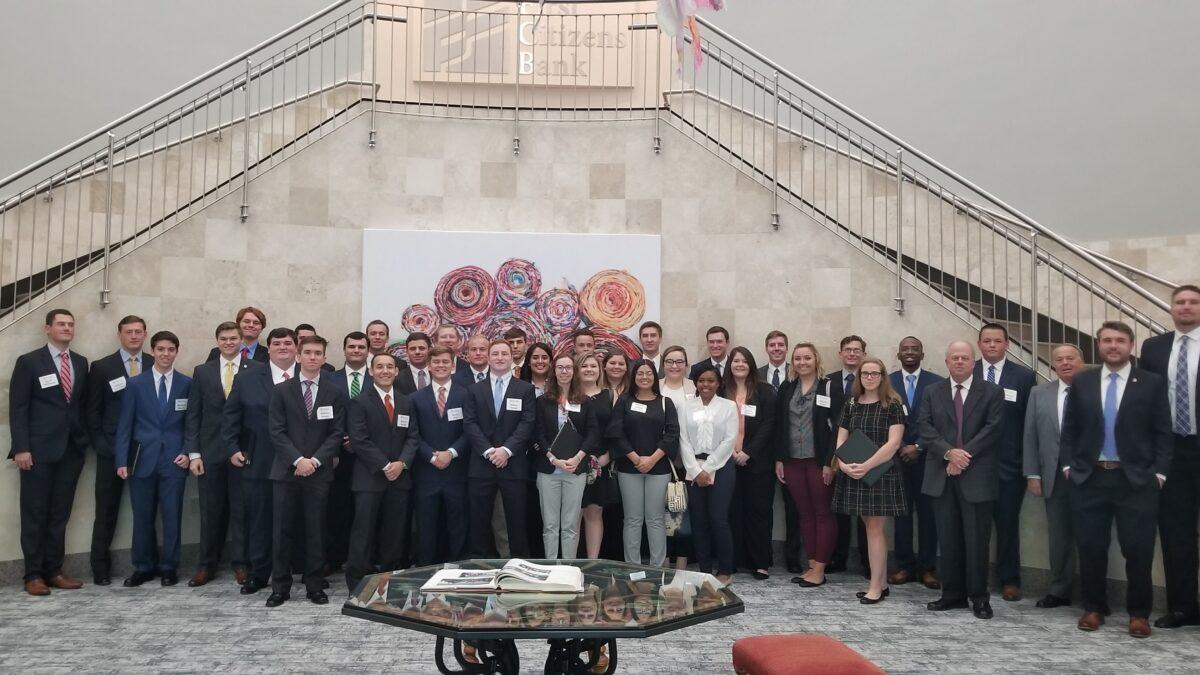 Group of 40 trust and wealth management majors in dark, professional attire stand in front of a marble staircase at First Citizens Bank.