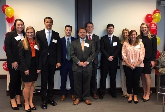 Group of ten students smile at camera in professional attire--these are the winners of the Wells Fargo scholarship.