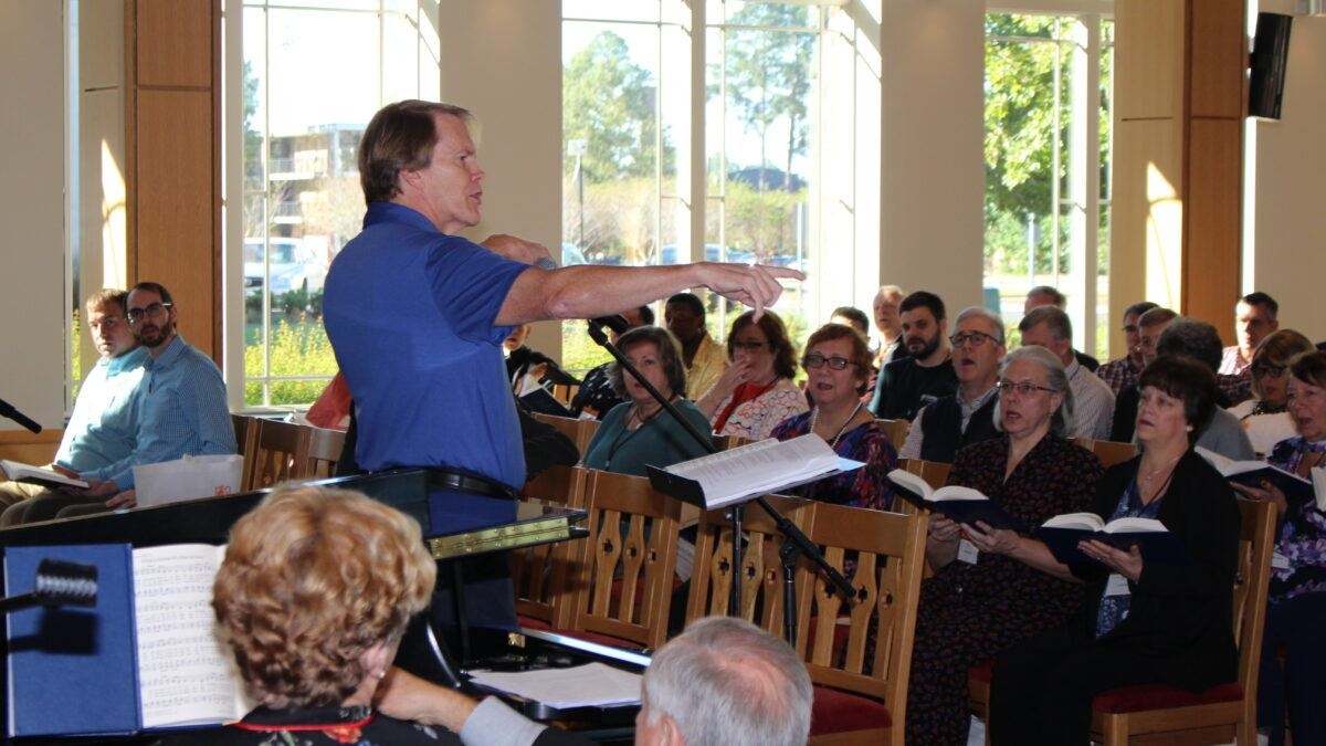 congregation holds hymnals and sings in front of conductor, a tall man in a blue polo shirt with his arms extended