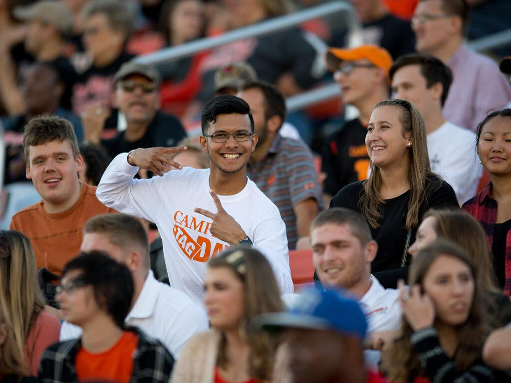 smiling male student in football stands gives two peace signs.