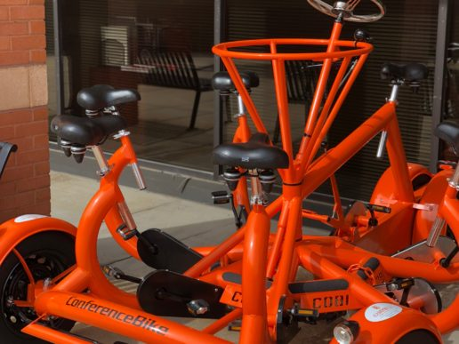 Photo of the law school's new orange conference bike that seats seven.