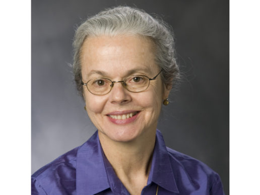 head shot of Ellen Smith, smiling in a purple collared shirt. She is an older woman with grey hair pulled back and wire-frame glasses.