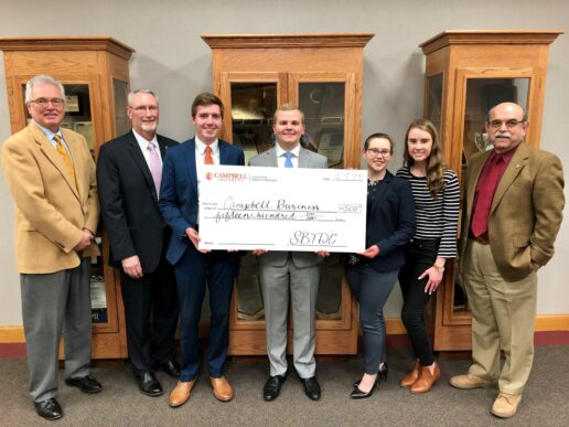 Dean Wells and Jimmy Witherspoon stand with Wells Fargo representative. The dean holds one half of a giant check as they accept the gift on Campbell's behalf.