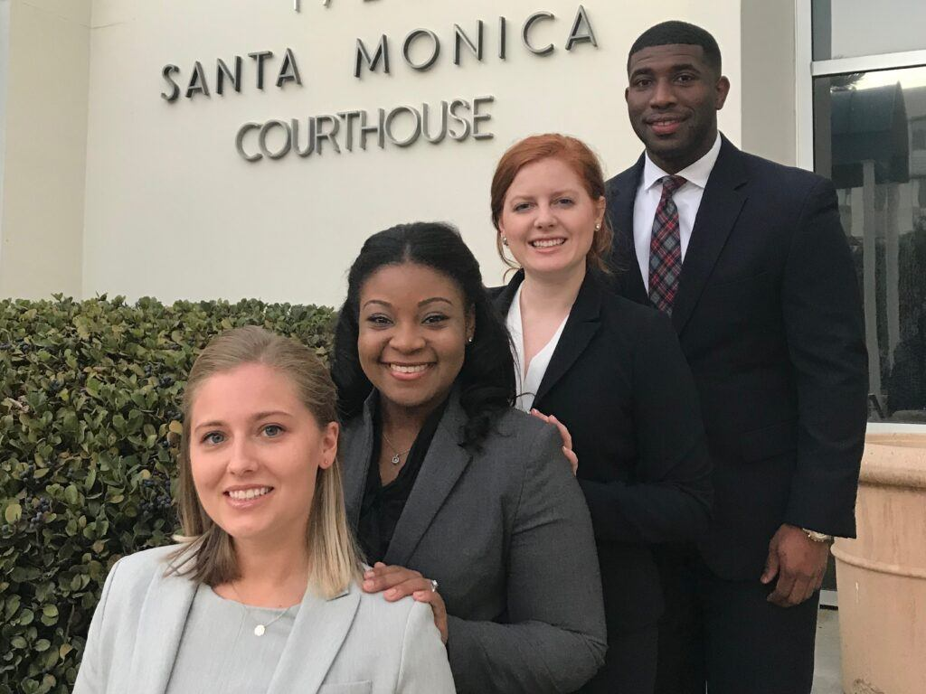 Photo of four law student advocates lined up on steps in front of the Santa Monica Courthouse.