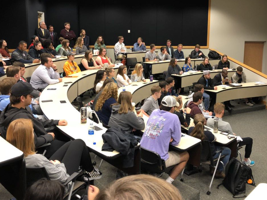 Guest speaker John Knapp stands in a full classroom