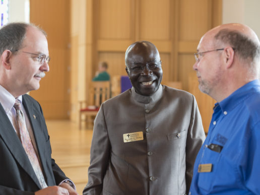 image of Dr. Caleb O. Oladipo standing between dean Andy Wakefield and a Divinity School staff member