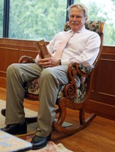 Photo of Dean J. Rich Leonard sitting in former U.S. Supreme Court Justice John Marshall's chair, which has been donated to the law school.