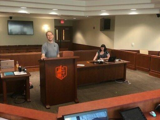 Photo of third-year law student Derek Dittmar practicing for the Jessup Moot Court Competition in one of Campbell Law's courtrooms.