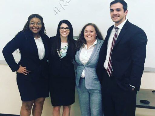 Photo of four law students standing in front of a white wipeboard with the hashtag in front of the words Roll Humps