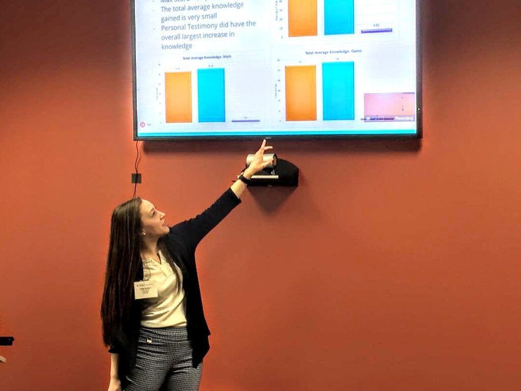 female student points to board during presentation