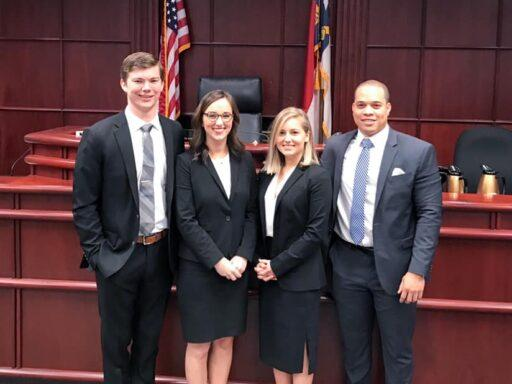 Photo of the four law students who won the AAJ Regional Championship posing in a Wake County Court room.