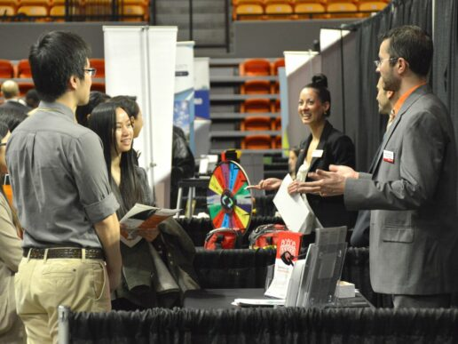 students surround a booth at Career fair on the floor of Gore Arena