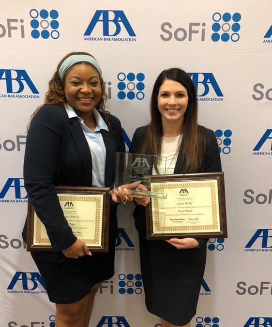 Photo of two female law students posing before ABA logos on a backdrop holding national title awards