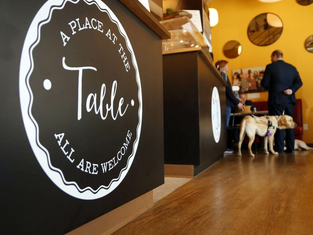 Photo of A Place At The Table restuarant logo with students and service dogs in background