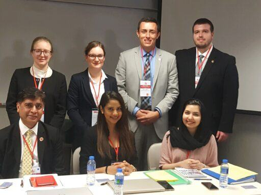 Photo of four Campbell Law students standing behind their three judges sitting at a table at the Vis Competition in Hong Kong