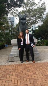 Photo of Vis competitors, a woman and man, standing in front of a dragon statue in Hong Kong.