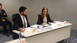 A male student on the left and a female student on the right sit at a table at the Vis competition in Hong Kong and appear to go over their notes.