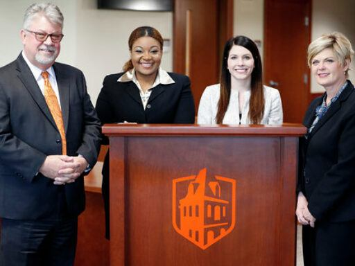 Photo of International Client Counseling Team and coaches posing at wooden lectern with Campbell Kivet logo displayed in orange