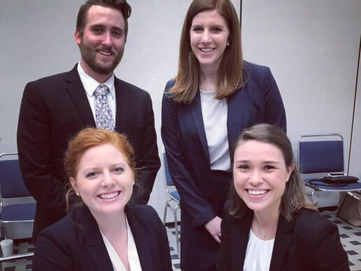 Group of four law student advocates pose two sitting at desks and two standing