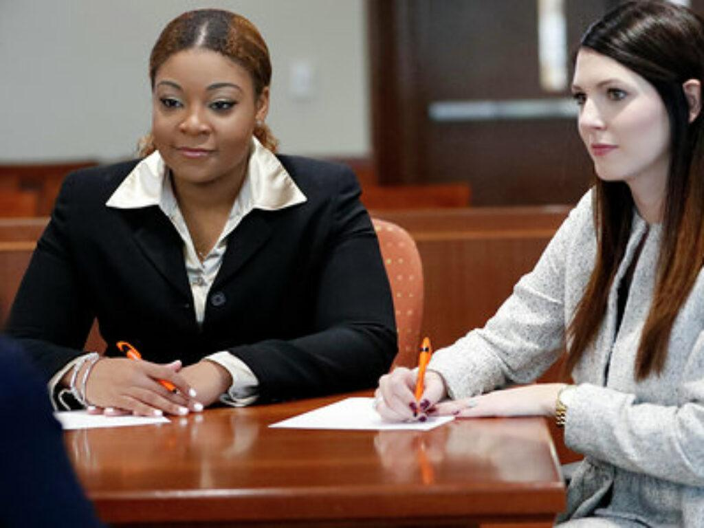 Photo of world champions Tatiana Terry and Katie Webb sitting at courtroom table