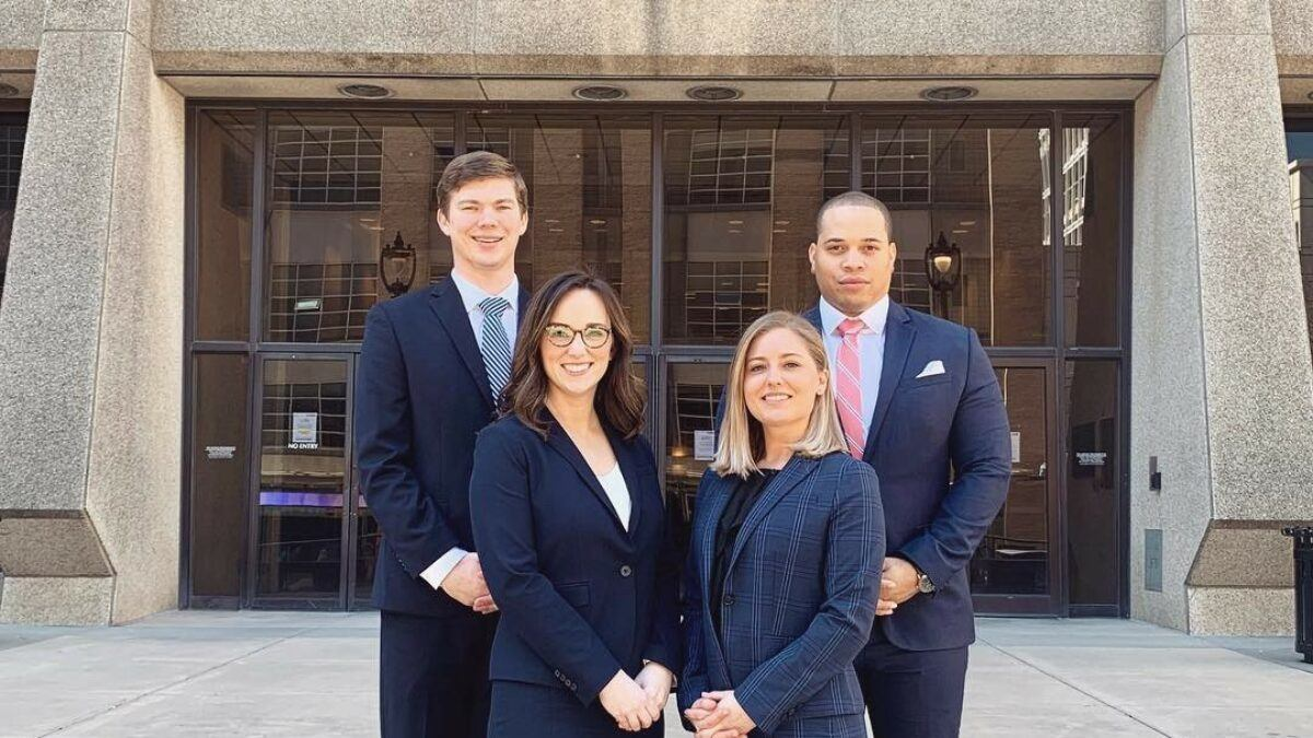 Photo of four Campbell Law AAJ National Trial Advocates posing in front of Wake County Courthouse