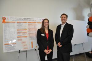 Dr. Dustin Wilson and student with poster